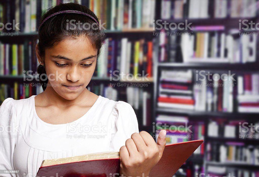 Indian Teenager Girl Studying In A Library With Bookshelf Stock Photo