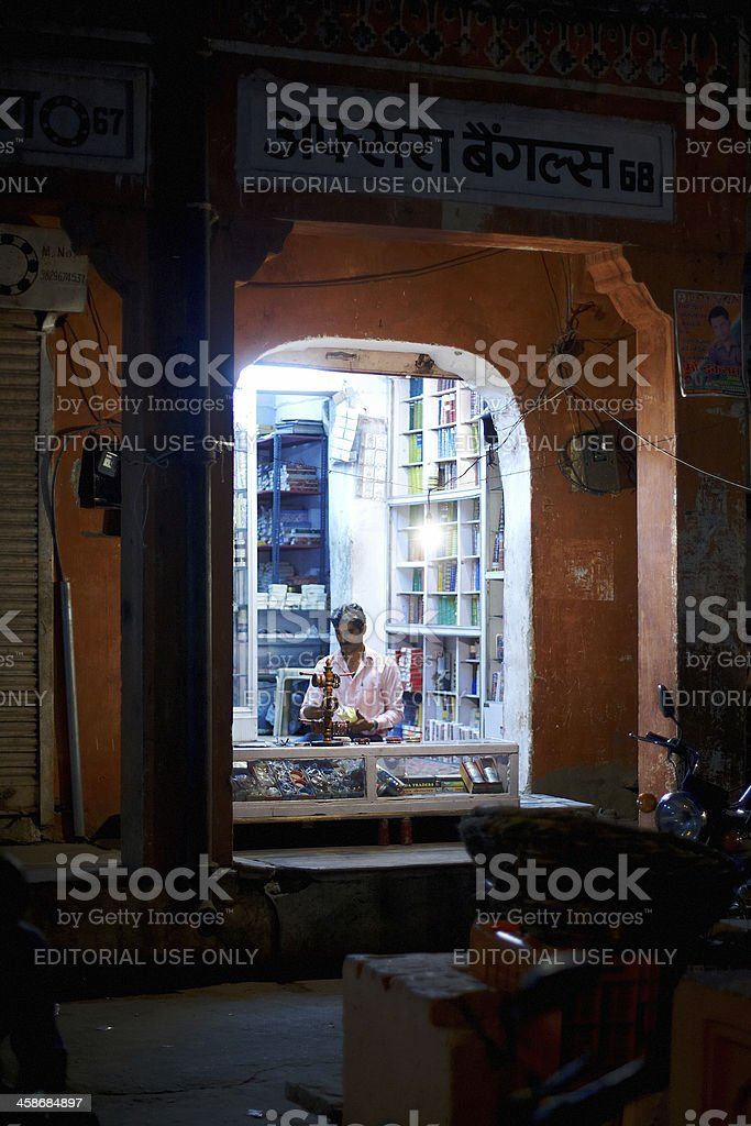 Indian trader working in his store at night royalty-free stock photo