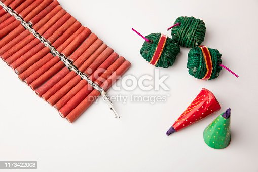 Indian Traditional Fire crackers with sweet during Diwali festival on white.