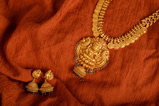 Indian Traditional Gold Necklace with earrings shot in studio light.