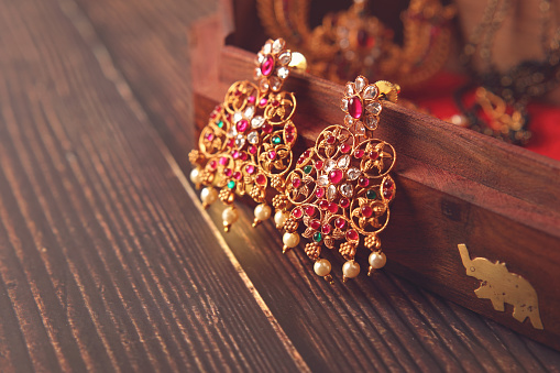 Indian Traditional Gold Wedding Earrings on wooden box