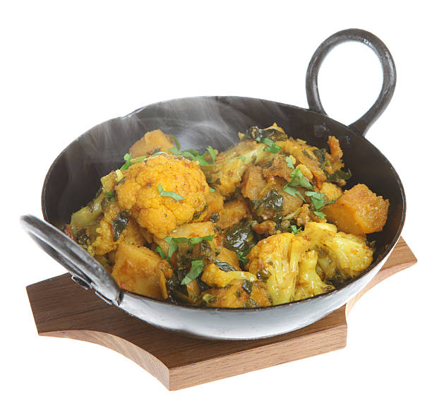 Indian Vegetable Curry Indian vegetable curry with cauliflower, spinach and potatoes (all gobi saag) with steam rising balti dish stock pictures, royalty-free photos & images