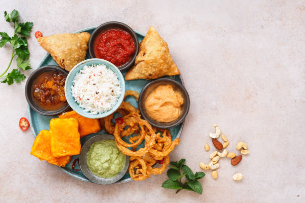 indian vegetarian thali  with jeera  rice, different snacks and dips - samosa stock photos and pictures