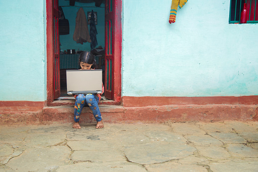 School girl of Indian ethnicity seating at corridor with laptop . Coronavirus Outbreak. Lockdown and school closures. Indian school small girl watching online education classes at home. COVID-19 pandemic forces children online learning.