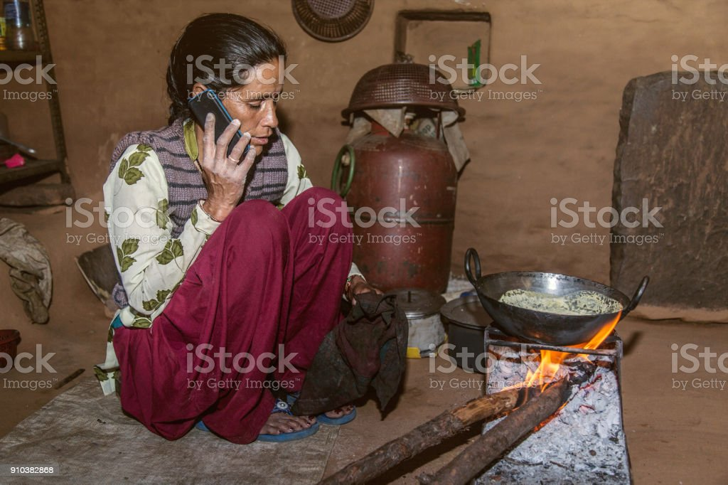 Indian village woman preparing food and talking on phone stock photo