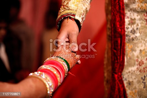 Indian groom holding bridal hand whe she coming on the stage. Weddings in India vary regionally, the religion and per personal preferences of the bride and groom. They are festive occasions in India, and in most cases celebrated with extensive decorations, colors, music, dance, costumes and rituals that depend on the religion of the bride and the groom, as well as their preferences.