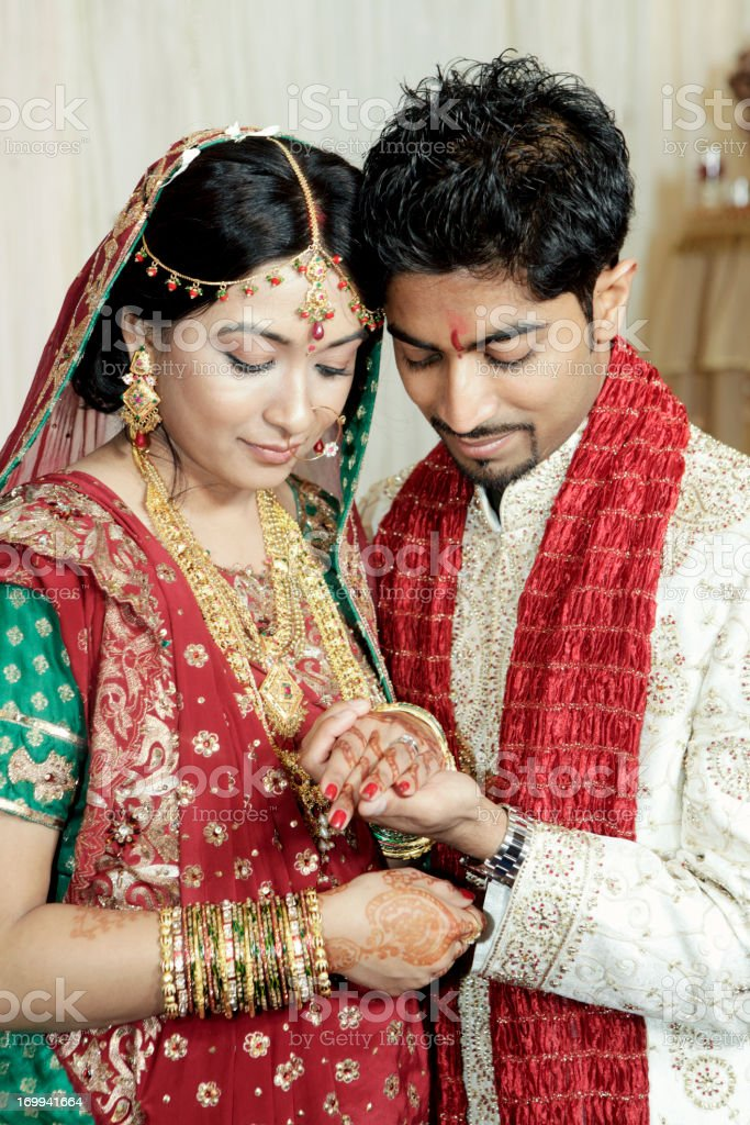 Indian Wedding Couple Looking At Rings Royalty Free Stock Photo