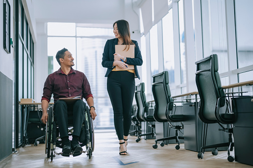 Indian white collar male worker in wheelchair having cheerful discussion conversation with his female asain chinese colleague coworking at walkway corridor