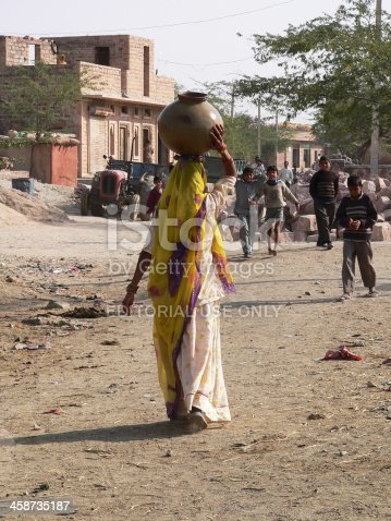 istock Indian woman bringing water to the village Chandelao, Rajasthan, India 458735187