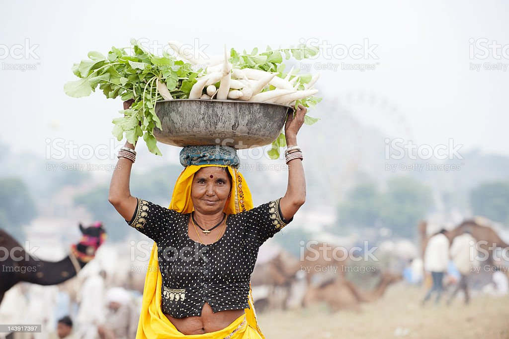 Indian woman carrying a big bowl of mooli royalty-free stock photo