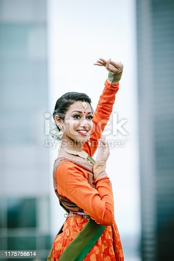 A beautiful smiling young woman dances and poses in traditional Indian makeup, accessories, jewelry, and clothing.  The setting is an urban rooftop in Seattle, Washington, USA.