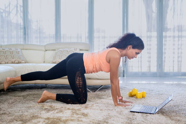 Indian woman doing yoga exercises with laptop stock photo