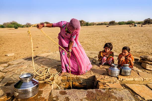 indische frau zeichnung wasser aus der gut, wüste, rajasthan - was bringt unglück stock-fotos und bilder