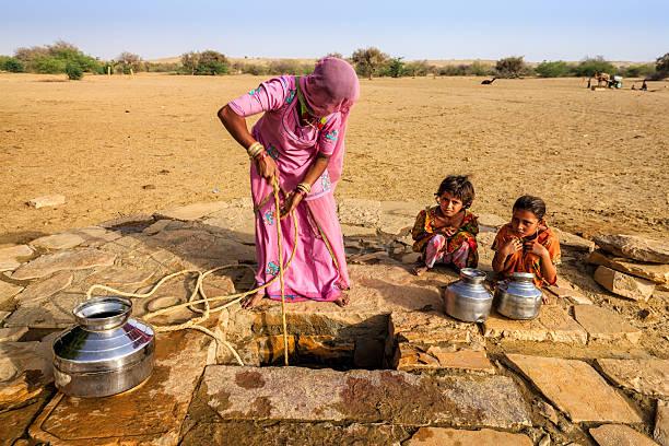 indian woman drawing water from the well, desert, rajasthan - kuraklık stok fotoğraflar ve resimler