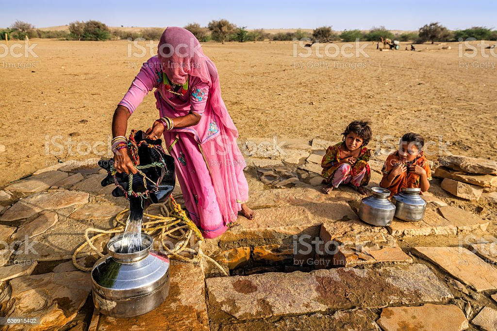 Indian woman drawing water from the well, desert, Rajasthan stock photo