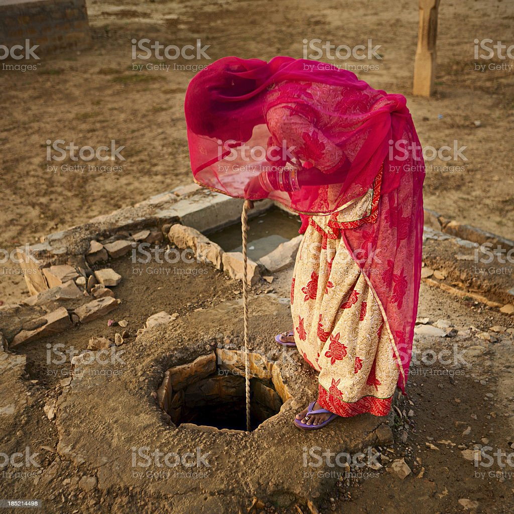 Indian woman getting water from the well. Rajasthan, Thar desert stock photo