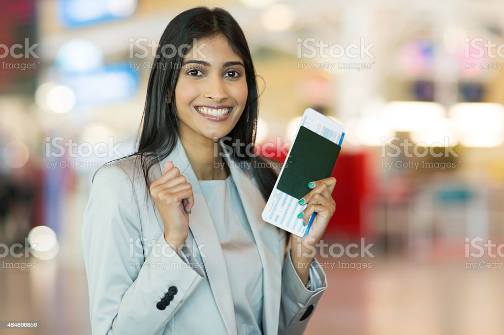 indian woman holding passport and boarding pass stock photo