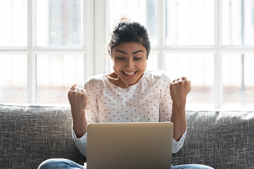 Indian woman in anticipation online lottery result holds fists together hopes for luck, girl holding pc on lap feeling excitement got loan opportunity from bank, sale big discount better offer concept