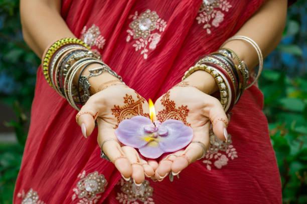 indische frau in traditionellem sari-kleid mit henna-tattoo-halten brennende lotus-kerze - indische kultur stock-fotos und bilder