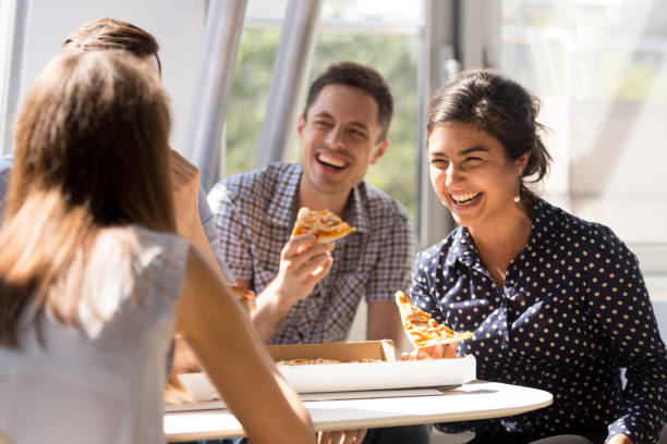 Indian woman laughing, eating pizza with colleagues in office stock photo