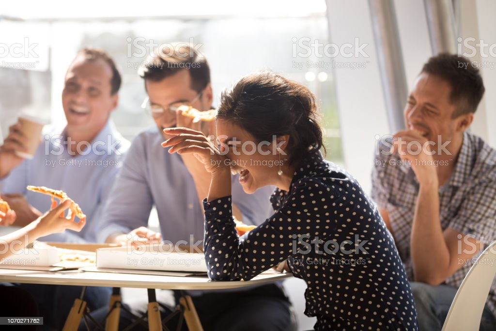 Indian woman laughing eating pizza with diverse coworkers in office royalty-free stock photo