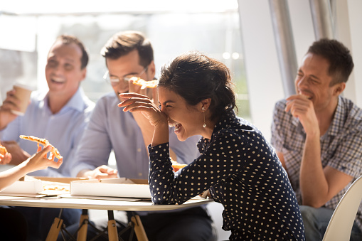 istock Indian woman laughing eating pizza with diverse coworkers in office 1070271762