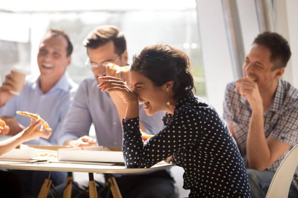 indyjska kobieta śmieje się jedząc pizzę z różnymi współpracownikami w biurze - przyjaźń zdjęcia i obrazy z banku zdjęć