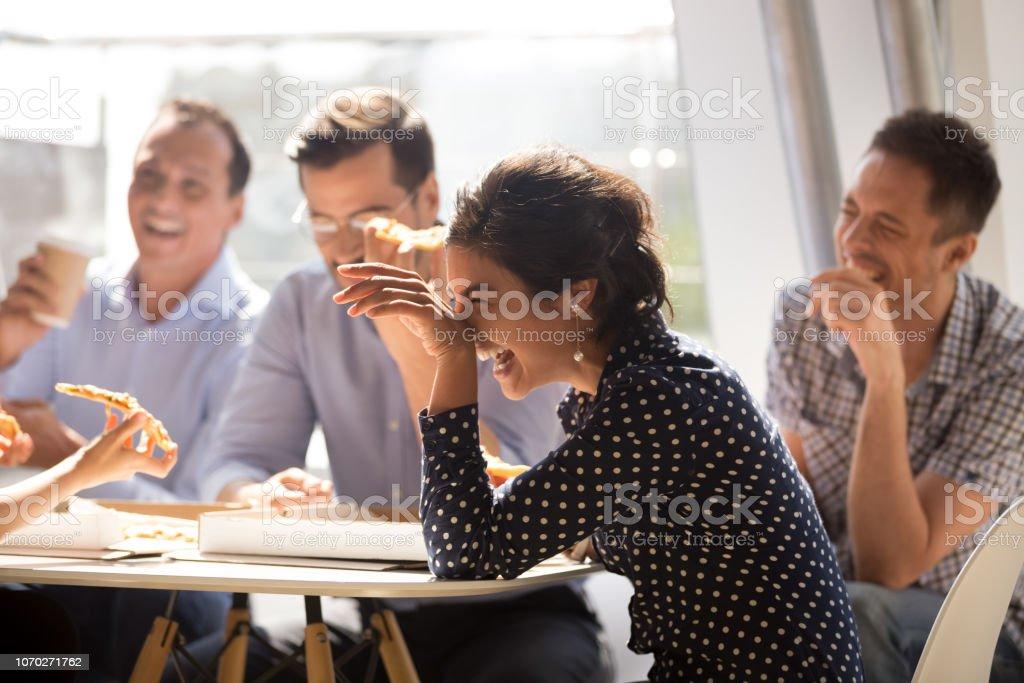 Indische Frau lachend Essen Pizza mit verschiedenen Kollegen im Büro – Foto