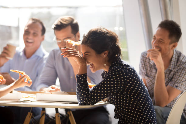 indian woman laughing eating pizza with diverse coworkers in office - people imagens e fotografias de stock