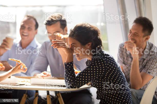 Indian woman laughing at funny joke eating pizza with diverse coworkers in office, friendly work team enjoying positive emotions and lunch together, happy colleagues staff group having fun at break