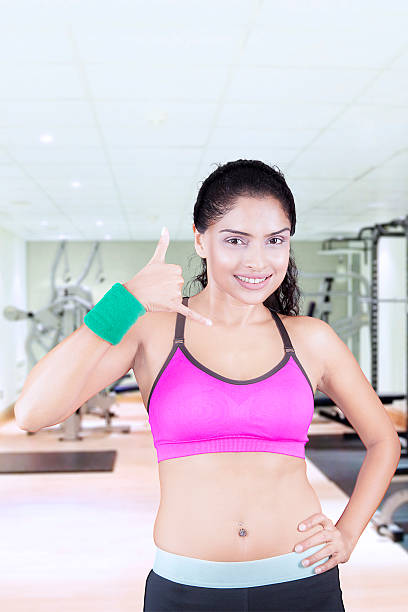 indian woman makes a call gesture at gym - call center stockfoto's en -beelden