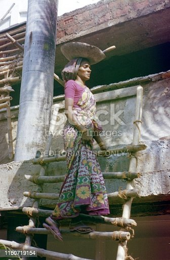 India (exact location unfortunately not known), 1978. Indian woman on a bamboo ladder carries a bowl of mortar to a construction site.