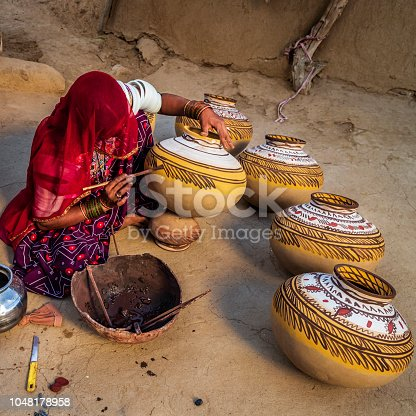 Indian woman painting water pots in her workshop, desert village in Rajasthan, India