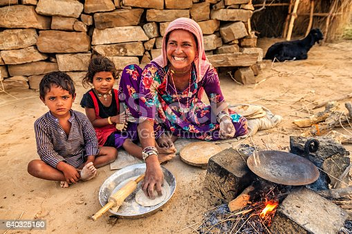 Indian woman preparing food - chapati, flatbread, desert village, India. Her children are waiting for breakfast just next to her