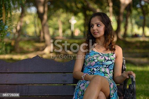 Indian woman sitting in park horizontal shot