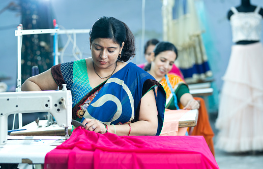 Female dressmaker cutting dress fabric on production line with sewing machine