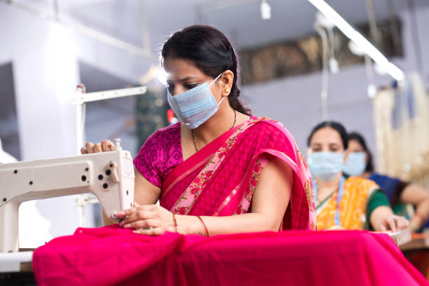 Indian woman textile workers with protective face mask on production line stock photo