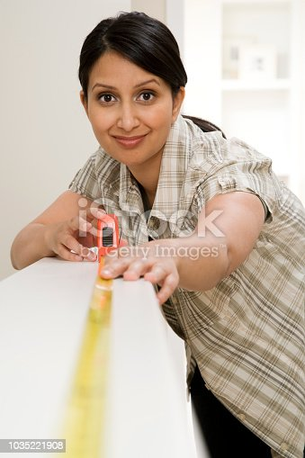 Indian woman using tape measure