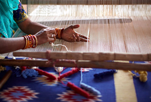Indian woman weaving by hand on a loom Woman waving a carpet on a manual loom in India craft product stock pictures, royalty-free photos & images