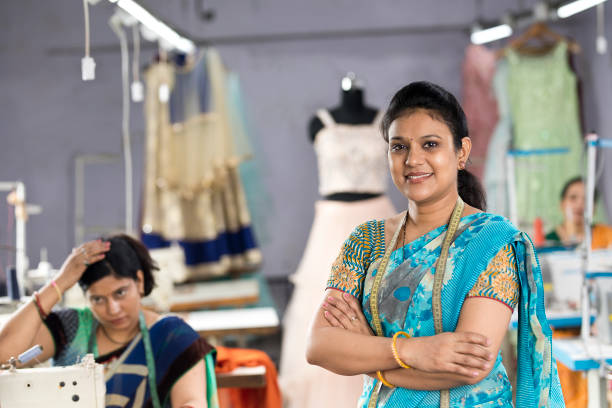 Indian woman with arms crossed at textile factory stock photo