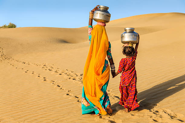 Indian woman with little daughter carrying water from well Indian mother and her little daughter crossing sand dunes and carrying on their heads water from local well, Thar Desert, Rajasthan, India. Rajasthani women and children often walk long distances through the desert to bring back jugs of water that they carry on their heads.  developing countries stock pictures, royalty-free photos & images
