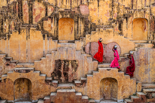 Indian women carrying water from stepwell near Jaipur, Rajasthan, India. Women and children often walk long distances to bring back jugs of water that they carry on their head.  Stepwells are wells in which the water may be reached by descending a set of steps.