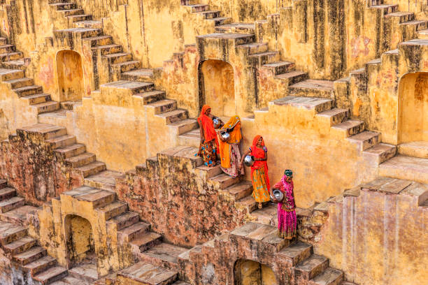 indian women carrying water from stepwell near jaipur - индия стоковые фото и изображения