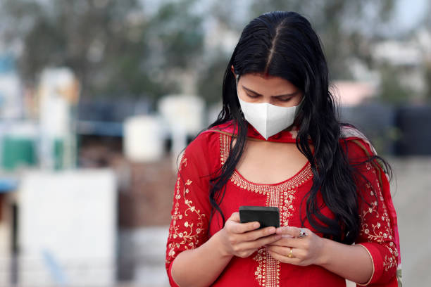 Indian women covering her face with pollution mask for protection against COVID-19 and using mobile phone stock photo
