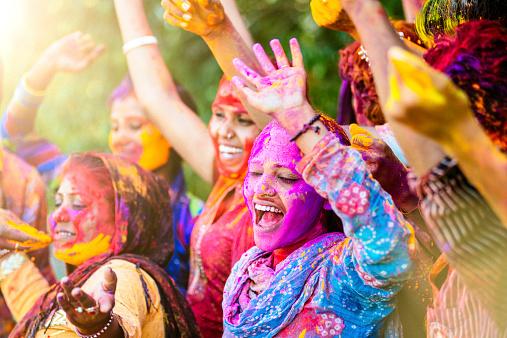 Indian women throwing colored Holi powder