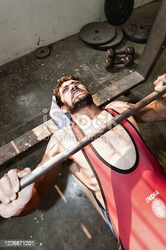 Indian Wrestler training his muscles in old rotten training backyard room in downtown New Delhi. Pushing weights lying on his back on metal construction weight bench. The India Logo on his shirt is a generic part of the Indian National Flag. New Delhi, India, Asia.
