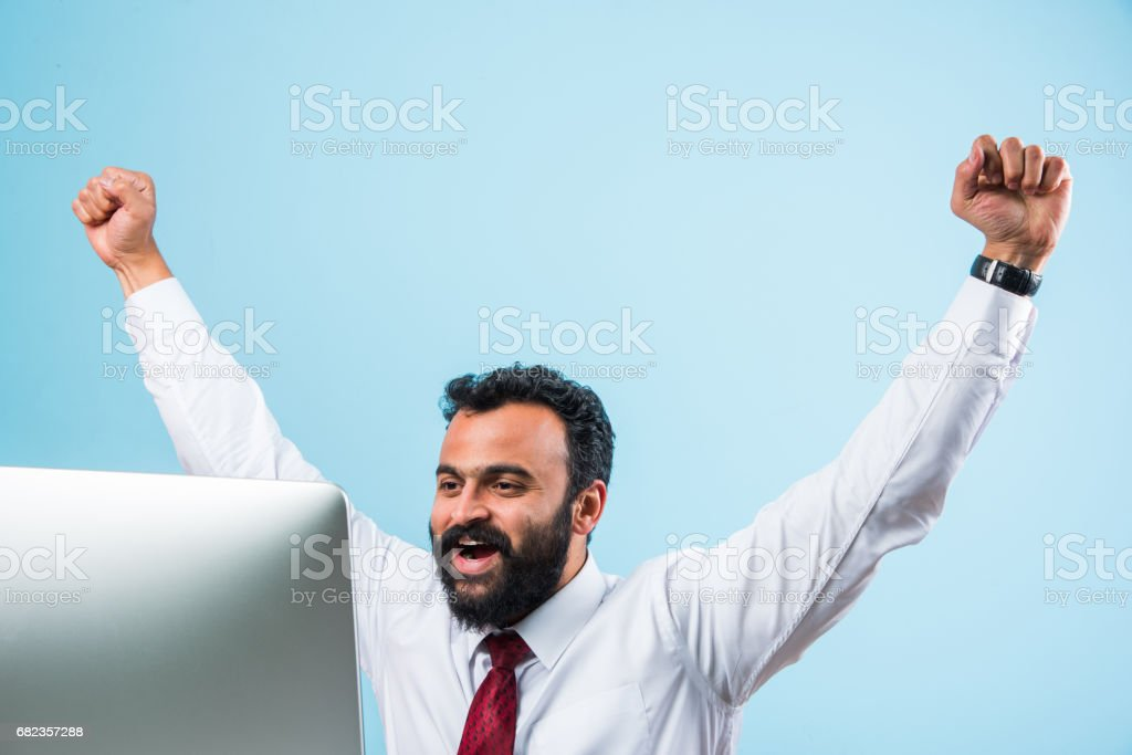 indian young and trendy looking or hipster businessman in office wear in beard using smartphone or computer royalty free stockfoto