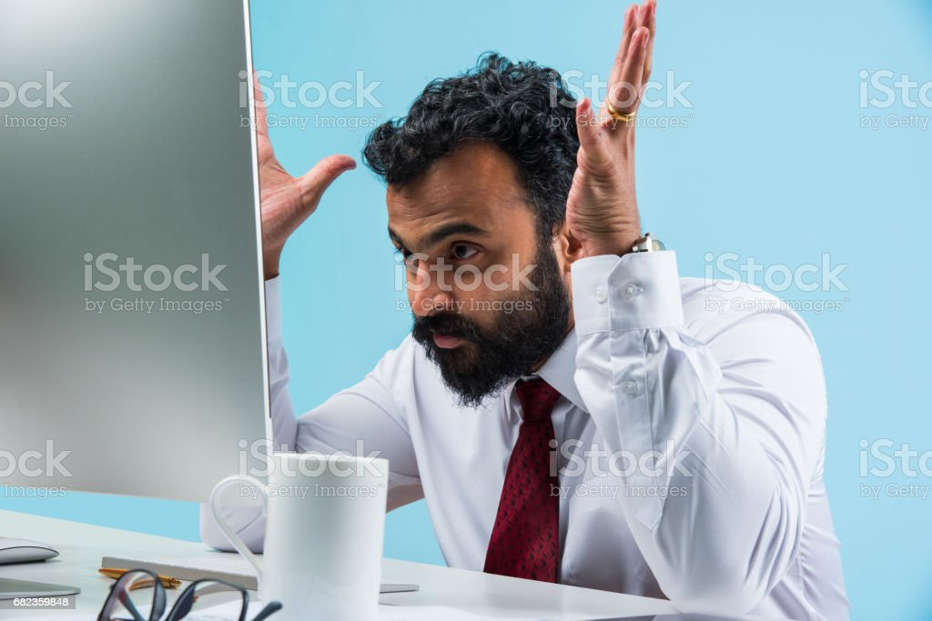 indian young and trendy looking or hipster businessman in office wear in beard using smartphone or computer zbiór zdjęć royalty-free