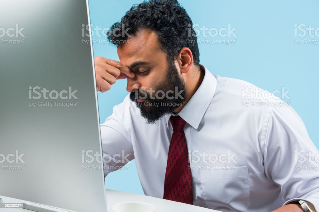 indian young and trendy looking or hipster businessman in office wear in beard using smartphone or computer foto stock royalty-free