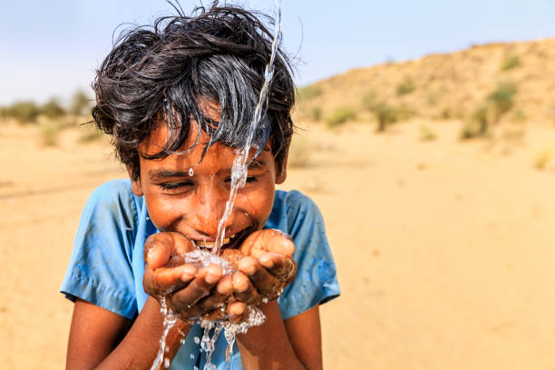 Indian young boy drinking fresh water, desert village, Rajasthan, India Indian young boy is drinking fresh water, desert village, Thar Desert, Rajasthan, India. Potable water is very precious on the desert - Rajasthani women and children often walk long distances through the desert to bring back jugs of water that they carry on their heads. developing countries stock pictures, royalty-free photos & images